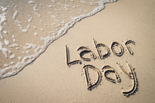 Labor Day Message Handwritten On The Smooth Sand Of An Empty Beach With An Oncoming Wave