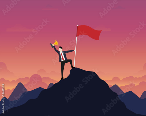 Carta da parati Businessman holding up a gold trophy cup with success flag on top of mountain