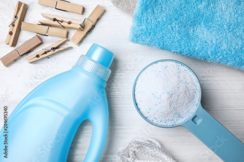 Photo Flat lay composition with laundry detergents, clothespins and towels on white wo