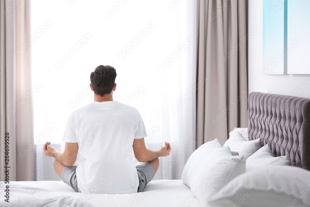 Fototapety, obrazy: Man meditating on bed at home. Zen concept
