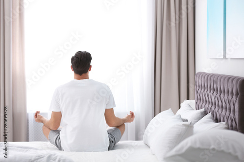 Man meditating on bed at home. Zen concept