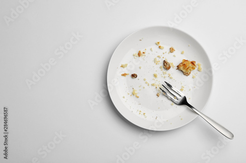 Fotografie, Obraz Dirty plate with food leftovers and fork on white background, top view