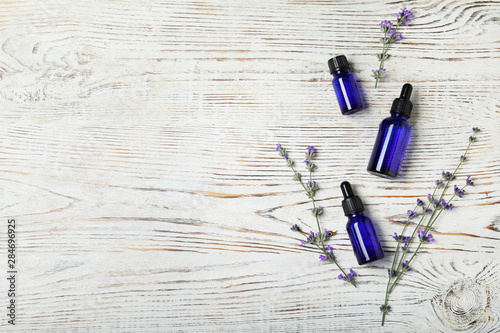 Fotobehang Bloemenwinkel Bottles of essential oil and lavender flowers on white wooden background, flat lay. Space for text
