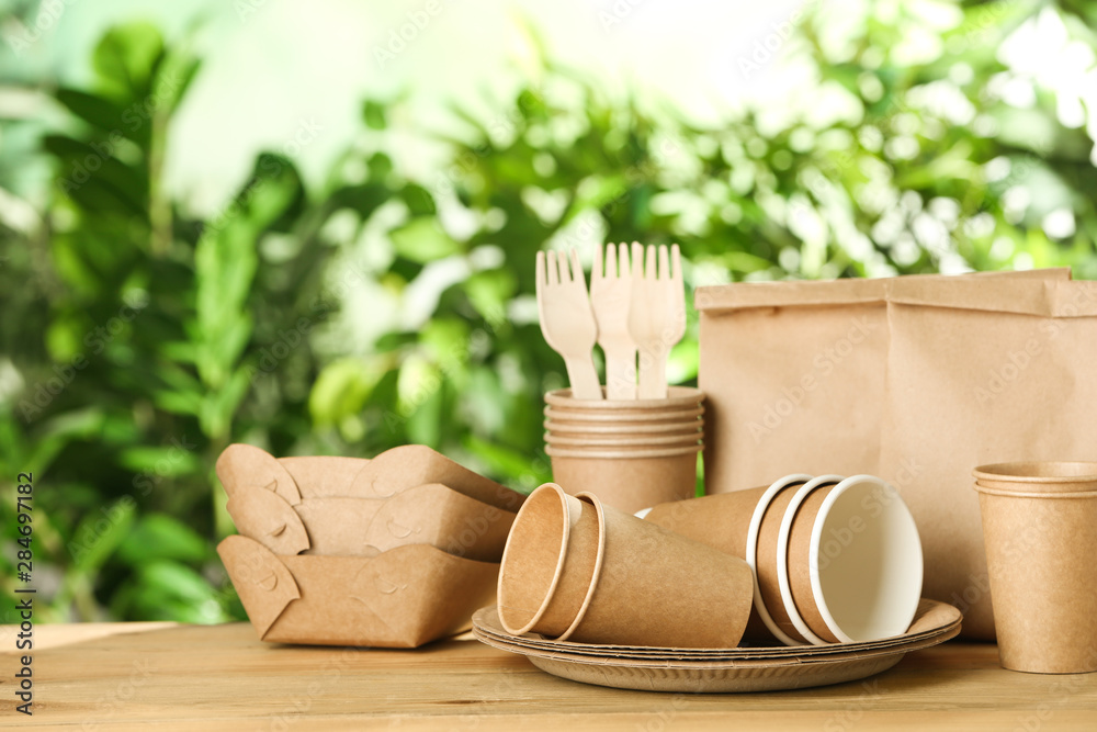Fototapeta Paper dishware on wooden table against blurred background, space for text