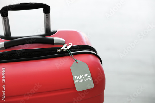 Stylish suitcase with travel insurance label on light background, closeup Canvas Print