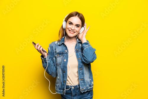 Foto  Happy cheerful woman wearing headphones listening to music from smartphone studi
