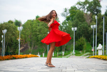 Young Beautiful Girl In Red Dress Walking On The Summer Street