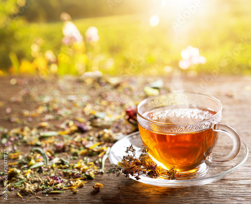 Cup of herbal tea with various herbs at sunset