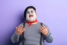 Close Up Of A Sad , Upset , Depressed Crying Clown With Raised Arms Looking Up, Isolated Blue Background, Studio Shot