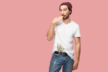 Tricky Handsome Bearded Young Hipster Man In White Shirt And Casual Hat Standing, Hold Many Dollars Money On The Pocket, With Unbelieveable Face. Indoor, Isolated, Studio Shot, Pink Background