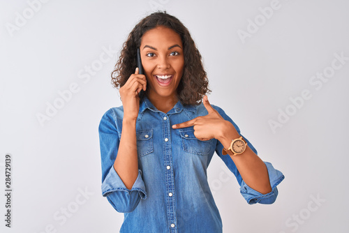 Fotomural  Young brazilian woman talking on the smartphone standing over isolated white bac