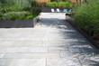 canvas print picture - Moderne Garten- und Terrassengestaltung im Materialmix: Terrasse und Gehweg aus Steinplatten umgeben von Schotter und Metall Pflanzgefäßen mit Grünpflanzen