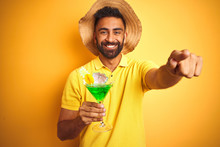 Indian Man On Vacation Drinking Cocktail Wearing Summer Hat Over Isolated Yellow Background Pointing With Finger To The Camera And To You, Hand Sign, Positive And Confident Gesture From The Front