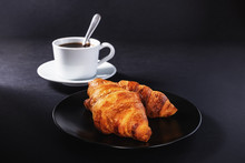 Cup Of Black Coffee And Croissant On Black