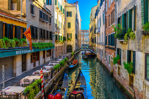 Foto auf AluDibond Venedig Narrow canal with gondola and tables of restaurant in Venice, Italy. Architecture and landmark of Venice. Cozy cityscape of Venice.