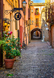 Fototapeta Uliczki - Cozy narrow street in Ferrara, Emilia-Romagna, Italy. Ferrara is capital of the Province of Ferrara