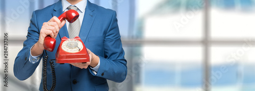 Businessman holding a vintage telephone