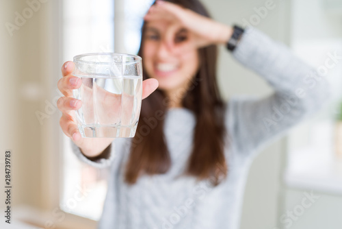Fototapeta  Beautiful young woman drinking a fresh glass of water with happy face smiling do