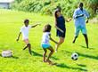 Leinwandbild Motiv Parents with children playing football