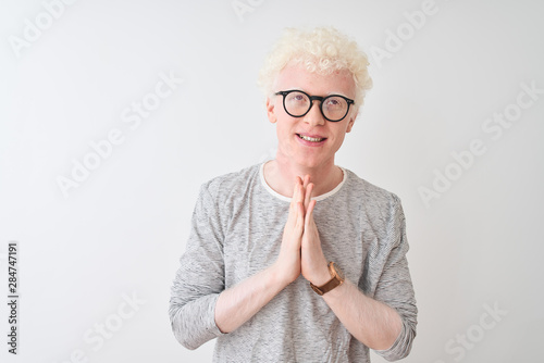 Valokuva  Young albino blond man wearing striped t-shirt and glasses over isolated white background praying with hands together asking for forgiveness smiling confident