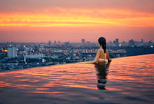 Young Woman Relax In Swimming Pool On Roof Top During Amazing Sunset And Enjoy Cityscape