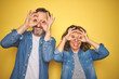 canvas print picture - Beautiful middle age couple together wearing denim shirt over isolated yellow background doing ok gesture like binoculars sticking tongue out, eyes looking through fingers. Crazy expression.