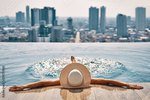 Back view of young woman in hat relaxing in swimming pool on the roof top of hotel