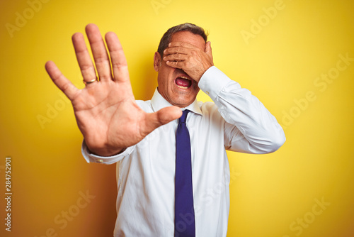 Cuadros en Lienzo  Handsome middle age businessman standing over isolated yellow background covering eyes with hands and doing stop gesture with sad and fear expression