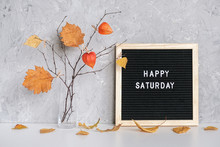 Happy Saturday Text On Black Letter Board And Bouquet Of Branches With Yellow Leaves On Clothespins In Vase On Table Template For Postcard, Greeting Card Concept Hello Autumn Saturday