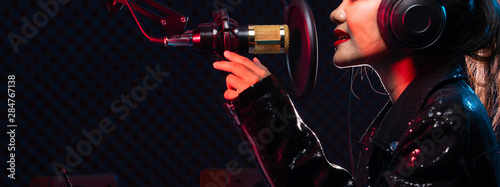 Foto  Asian Teenager Woman black hair earmuff headphone sing a song loudly power sound over hanging microphone condenser, speakers, composer note book and monitor