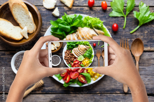 Foto  Hand hold smartphone woman takes photo healthy food for blog,photographer food