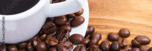 Coffee bean. On the background of wooden boards a cup of coffee and scattered...