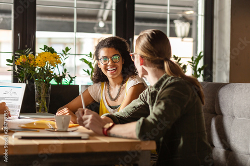 Joyful young woman talking with her friend Canvas Print