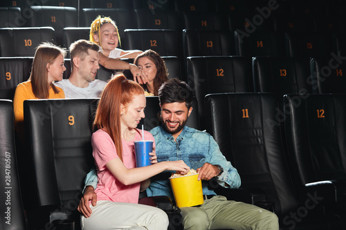 bearded happy guy treating his girlfriend with popcorn , looking after his girl Canvas Print