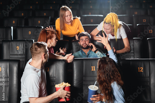 Fotografiet young people trying to explain their friend that it isn't allowed to talk on smart phone at the cinema