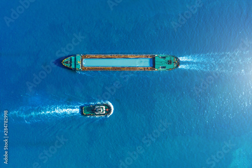 Cargo ship barge and tugboat sail to meet each other in the seaport of the port, aerial view Fototapeta