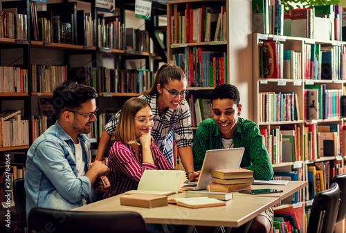 Foto Four young students study in the school library, female student using laptop for researching online