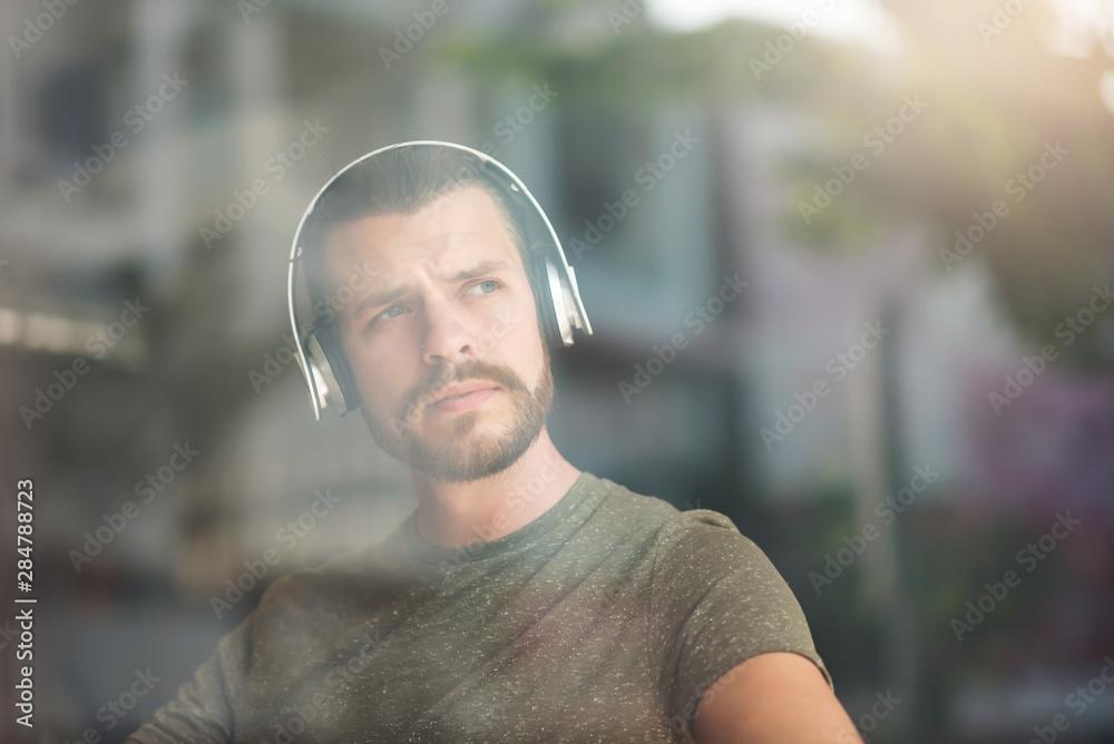 Fototapeta Portrait of bearded man listening to music with headphones.