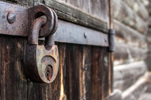 Old Hanging Rusty Iron Lock On Wooden Door