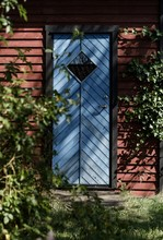 Closeup Vertical Shot Of A Blue Wooden Door Of A Small Red Barn In A Forest