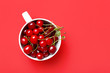 canvas print picture - Cup with ripe sweet cherry on color background
