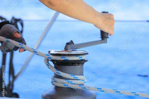 Fotografía  Yachtsman hands dealing with yacht ropes on halyard winch