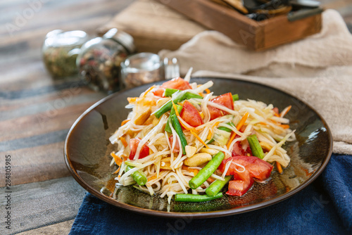 Traditional Thai food papaya salad prepared with fine slices of papaya, tomatoes, green beans and peanuts Wallpaper Mural
