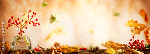Fotografía  Beautiful autumn red berries and oak leaves in glass bottle on wood  at bokeh background, front view