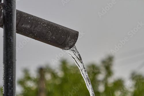 Water drains from a drainpipe during heavy rain Canvas-taulu