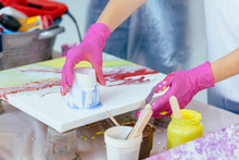 Woman Painter Creating Fluid Acrylic Abstract Painting In Art Therapy Class, Dropping Paints On Canvas.