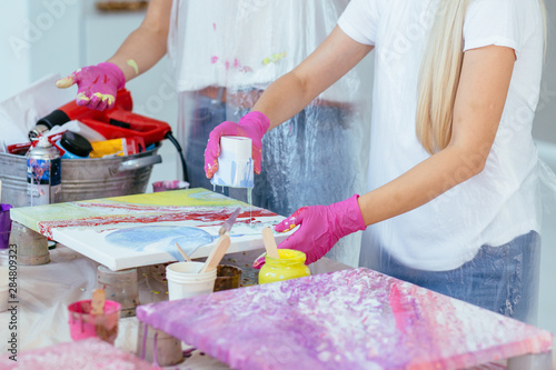 Woman painter holding hair dryer while female beginnres studying creating fluid acrylic abstract painting in art therapy class, dropping paints on canvas Canvas Print