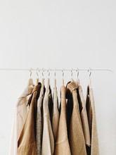 A Hanger Of Warm Beautiful Feminine Beige Sweaters Or Pullovers. Autumn, Fall, Winter, Fashion Concept. Empty Space, Mock Up. Minimal Background.