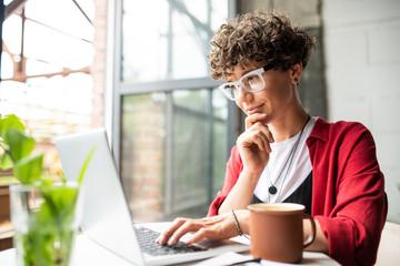 Busy young elegant woman in eyeglasses looking at laptop display