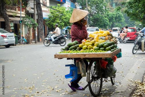 Fototapeta Vendor with bike of fruits on Hanoi street obraz na płótnie